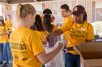ASU students stuffing lunch bags at a service event